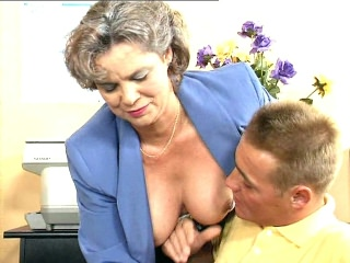 Kelly is training a young hunk in her office. But it seems like this hunk is more interested in her tits and starts squeezing and pinching her already erect nips. She doesn't mind as long as she gets to perform some oral examination and have him drill her hard.